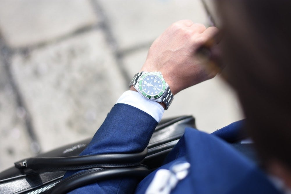 Photo of well-dressed person with watch, briefcase and sunglasses.