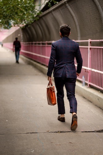 Photo of man walking away while carrying a luxury leather briefcase in brown.