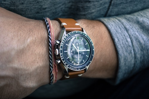 Photo of a man's wrist wearing a luxury wrist watch with a brown leather strap.
