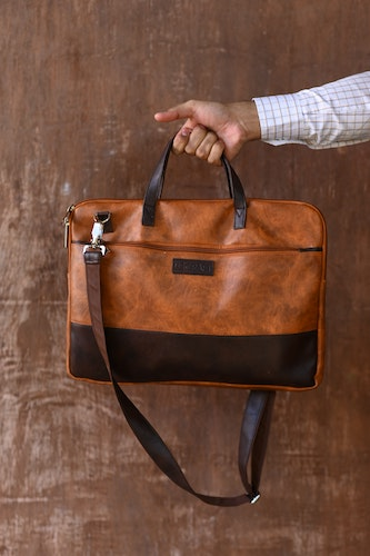Photo of luxury leather briefcase in brown with black trim.